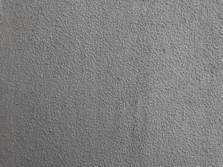 Exterior textured painted outside of the highrise building with beige color and looking like grey and making a rough undulating surface and painted after the completion of primer stucco first coating