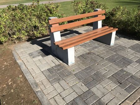 A wooden bench with concrete supports built in between the interlock floor tile flooring isolated for a healthy and relax conversation with friend or family relative in a park or outdoor