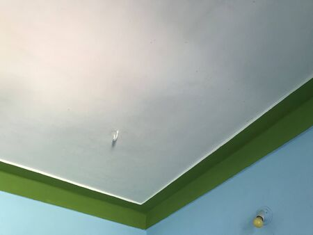 Emulsion painted concrete ceiling with White color and border by green color by a skilled painter to make residential house ceiling interior beautiful
