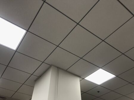 White calcium silicate Square Grid suspended false ceiling work for an office in an high rise buildings for large office spaces with LED lighting for better reflection