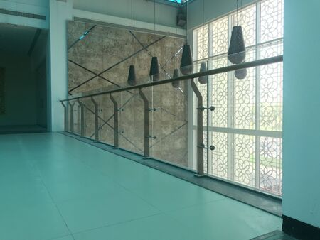 Stainless steel Glass handrail fixed on the pent floor balcony area with the blue color Vinyl or linoleum flooring for an high class Four star hotel interiors work