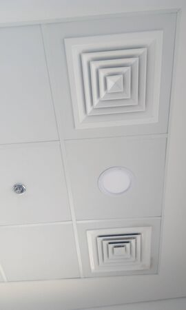 Grid and gypsum false ceiling interior tiles fixed along with Square shaped supply and return of air conditioning duct system of an office building