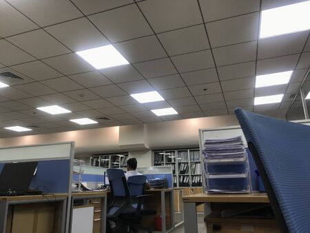 An Employee working in stress alone due to overload in office after the working hours in an office which is finished by Grid false ceiling furniture and all interior fit out works
