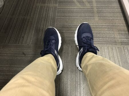An Employee wearing Casual or sports shoes instead of formal shoes in the office which is not giving appropriate look to an employee when he meets his manager Banco de Imagens