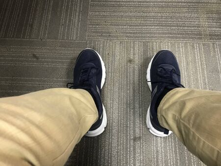 An Employee wearing Casual or sports shoes instead of formal shoes in the office which is not giving appropriate look to an employee when he meets his manager Imagens