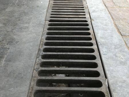 Channel gratings made of ductile iron material for drainage purpose at an car cleaning location so that dirty water runs towards through this gratings to manhole Foto de archivo