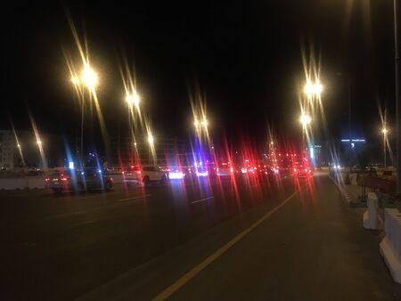 En mode week-end, célébrer le week-end en voiture sur une route urbaine avec des lampadaires scintillants et le centre-ville est génial pour se faire vibrer le mouvement des voitures de vitesse