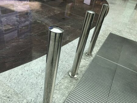 Escalator pole stainless steel finished fixed over the granite flooring next to the landing of Escalator platform