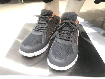 A pair of Sneakers wore by a garments toy for demo on a stainless steel and fixed rigid for marketing of Sports shoes for athletes