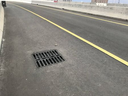 Heavy Duty grating Manhole Cover complied with British Standards fixed on a flyover Highway bridge for Drainage of Roads and Infrastructure areas and Tarmac roads with yellow line marking for lanes