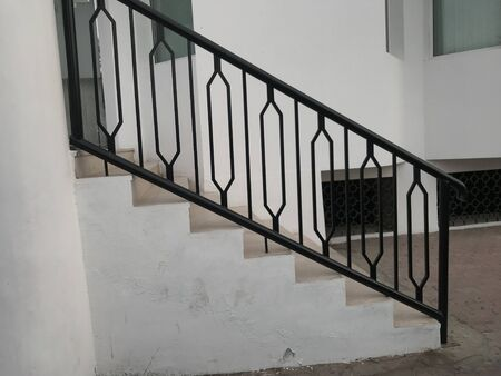 Black color enamel oil painted over the surface of galvanized iron or mild steel handrail or balustrade for an entrance for an handicapped access ramp for an public building or hospital