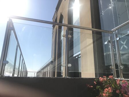 Stainless steel glass transparent handrails with hairline finish fixed at lobby or entrance of multistory buildings and sky background visible with white clouds Foto de archivo