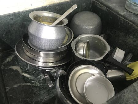 Uncleaned Aluminum and silverware kitchen utensils are kept inside the granite finishes Sink for cleaning by housewife and part of an chores or housework