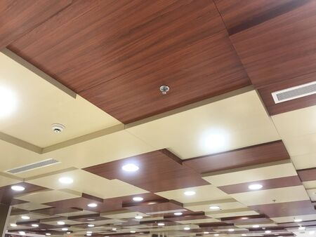 Wooden false ceiling with brown and yellow painted enamel paint with spot light and down lighting