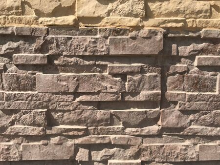 Stone pitching works for wall finishes of compound wall of an Residential villa House