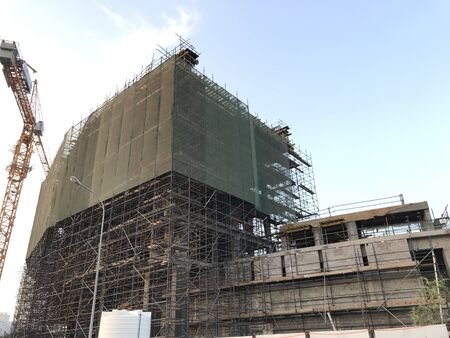 Building construction is in progress using installed tower crane and activities like concreting and reinforcement and scaffolding to del