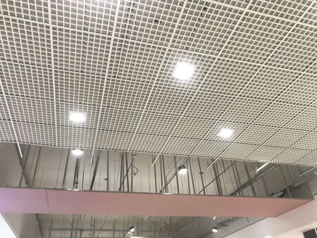 Macro Grid False ceiling around gypsum finished under progress which expose pink gypsum board furring channels supports and threaded rod Stock Photo