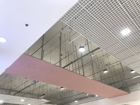 Macro Grid False ceiling around gypsum finished under progress which expose pink gypsum board furring channels supports and threaded rod