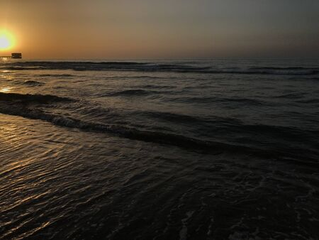 Evening Sunset at the beach muscat with background of running waves of ocean towards oman peninsula Foto de archivo