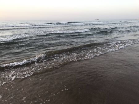 Evening Sunset at the beach muscat with background of running waves of ocean towards oman peninsula Archivio Fotografico