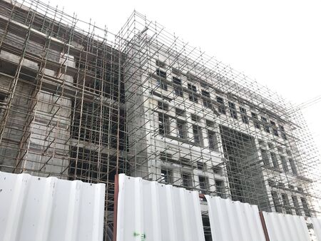 Building construction is in progress with installation of Scaffolding and shuttering at an structure completion stage and fencing using Corrugated steel