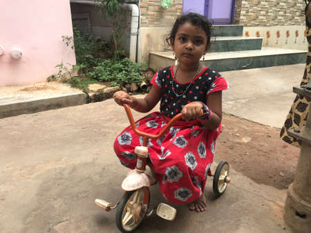A girl riding cycle alone in an fine evening and feeling bored while other children not available to have game and fun