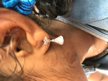 Small girl wearing silver made ear ring ornament for beauty enhancement
