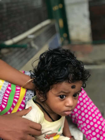 Indian baby boy with black curling hair with his baby sitter