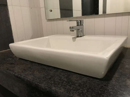 Beige ceramic or porcelain counter-top or table-top wash basin at the toilet above an granite counter platform 版權商用圖片