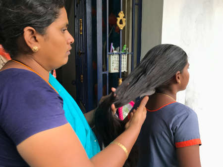 Mother or mommy combing her daughter who is being prepared herself to go school