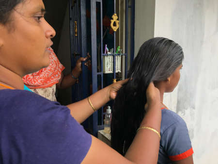 Mother or mommy combing her daughter who is being prepared herself to go school routine