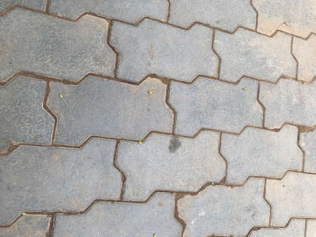 Grey color interlocking tiles pattern background tiles in the streets in which sand grouting done