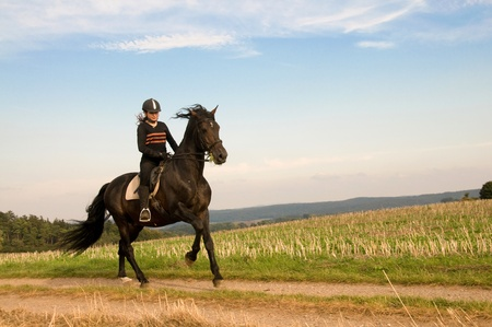 Equestrienne  rides at a gallop across the field. photo