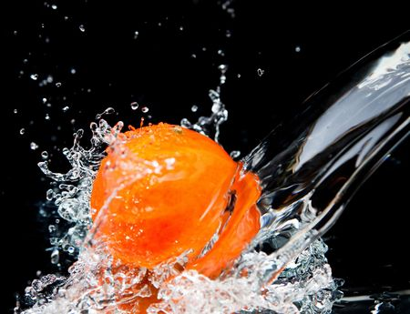 Orange and splash water over black background photo