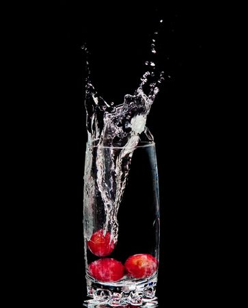 co action: Grapes and splash water over black background