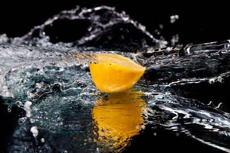 Lemon and splash water over black background Stock Photo - 6177417