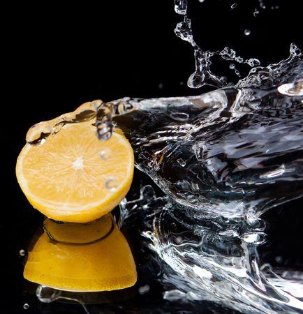 Lemon and splash water over black background Stock Photo - 6177462