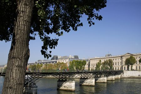 Pont des arts or passerelle des arts in Paris which crosses the Seine River with the Palais du Louvre in the background photo