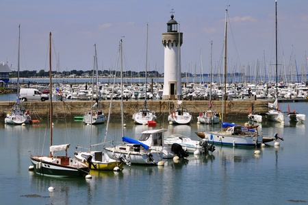 Port of Haliguen with red petunia flowers and the lighthouse at Quiberon in the Morbihan department in Brittany in north-western France