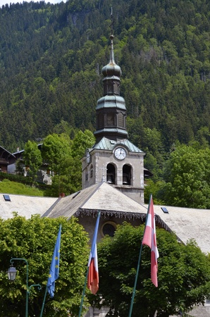 Bell tower of church of Morzine in the mountains of Alps in eastern France, commune in the Haute-Savoie department in the Rh�ne-Alpes region photo