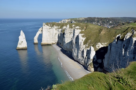 Cliffs of Etretat with the famous pointed  Aiguille   Needle  and the natural arche the  Porte d Aval   Etretat is a commune in the Seine-Maritime department in the Haute-Normandie region in northwestern France photo