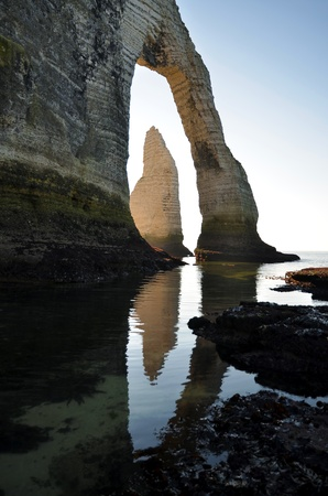 Famous pointed Needle and natural arche of  Porte d Aval  at low tide at Etretat, commune in the Seine-Maritime department in the Haute-Normandie region in northwestern France photo