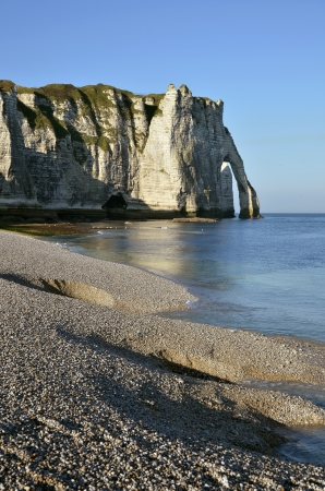 Famous pebble beach and cliff  d Aval  of Etretat, commune in the Seine-Maritime department in the Haute-Normandie region in northwestern France photo