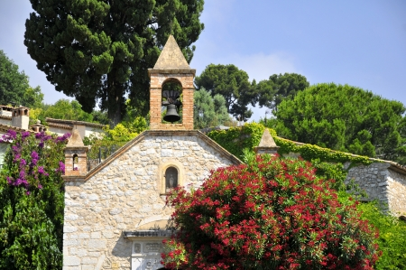 vence: Church of Saint Paul of Vence in southeastern France with red oleander flower in the foreground  Region Provence, department Alpes Maritimes Stock Photo
