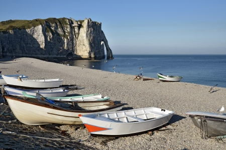 Small fishing boats on the famous pebble beach and cliffs of Etretat, commune in the Seine-Maritime department in the Haute-Normandie region in northwestern France photo