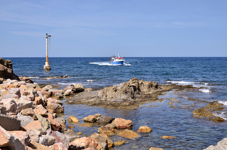 commune: Rocky coast and beacon with fishing boat of Banyuls-sur-Mer, commune on the \\\\\\\c?te vermeille\\\\\\\ in the Pyr?n?es-Orientales department, Languedoc-Roussillon region, in southern France. Stock Photo