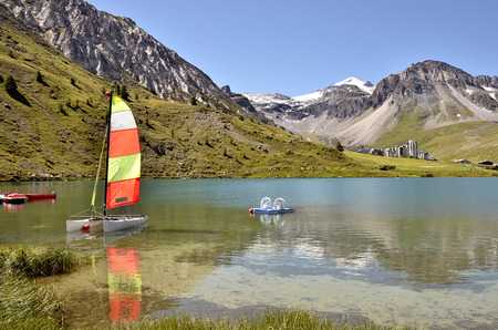 commune: Lake of Tignes with sailboat and pedalo and TignesVal Claret Village in the background. Tignes is a commune in the Tarentaise Valley in the Savoie department Rh DoAlpes Region in southeastern France Stock Photo