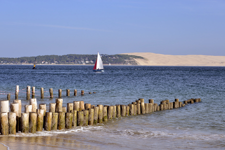 gironde department: Sea at CapFerret with sailboat and the Dune of Pilat in the Background. Commune in the Gironde department in southwestern France Stock Photo
