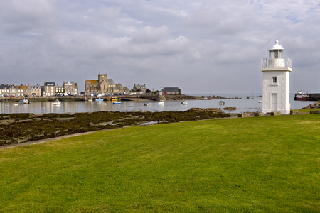 wrack: White lighthouse and church of Saint-Nicolas in the background of Barfleur, a town in the peninsula of Cotentin in the Manche department in Normandy in north-Lower western France