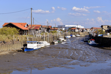 gironde department: Boats at low tide in the harbor of ostreicole Larros common is a Located on the shore of Arcachon Bay, in the Gironde department in southwestern France. Stock Photo